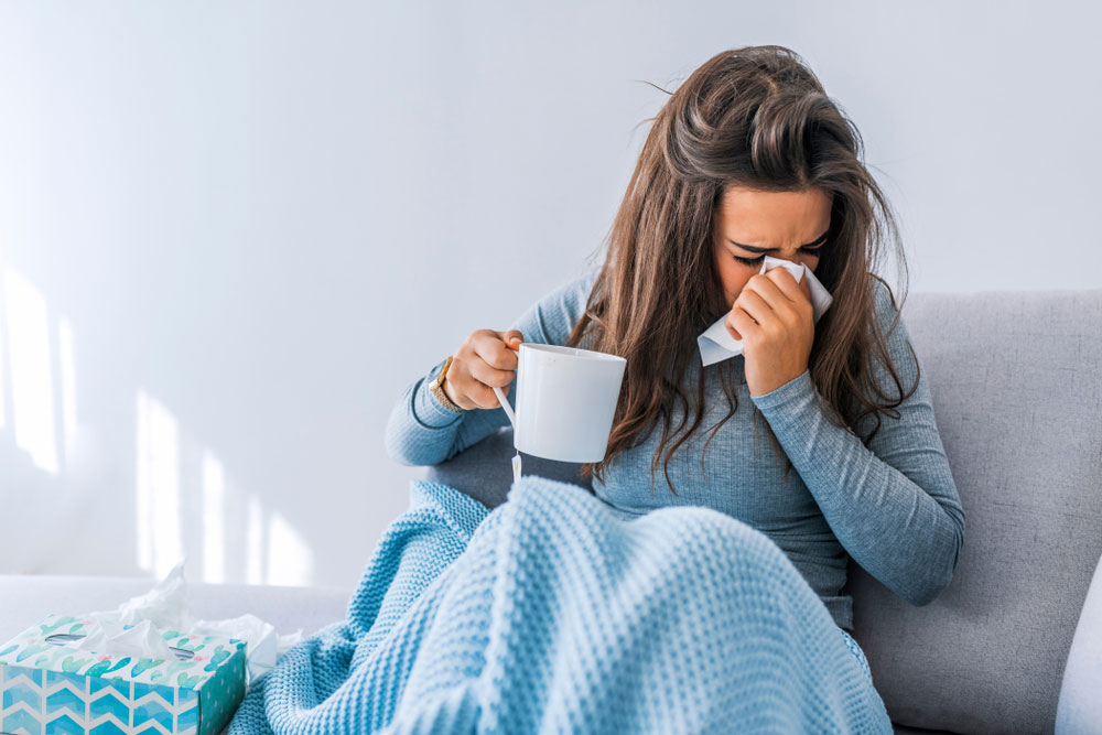 woman feeling sick on the couch drinking tea