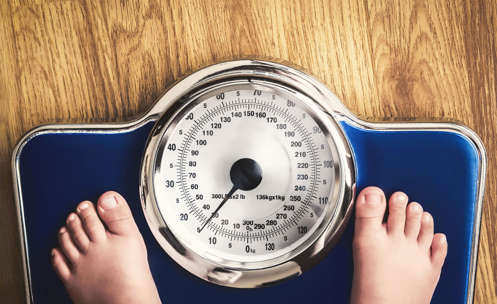 child weighing themselves on a scale