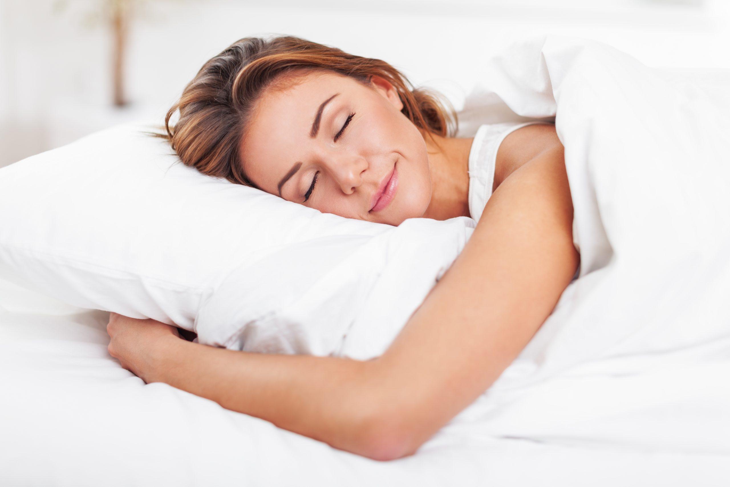 woman sleeping on white sheets