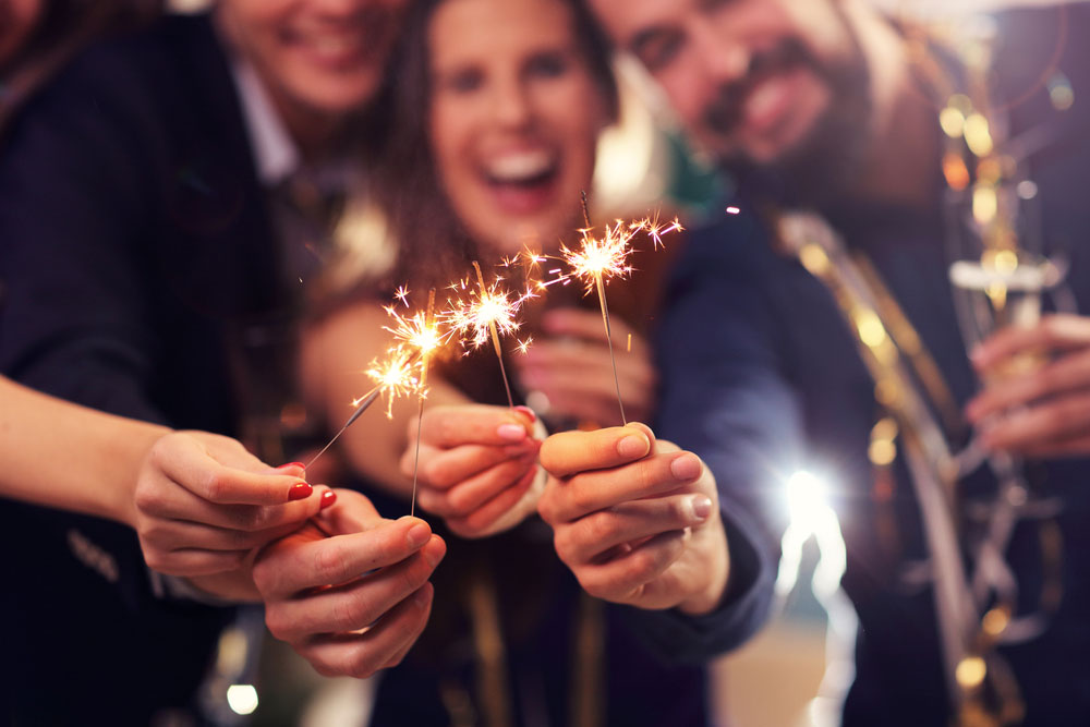 a bunch of friends holding sparklers