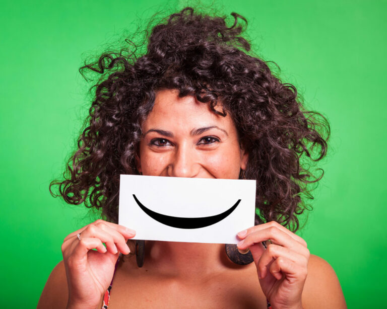woman holding paper over her face with a smile on it