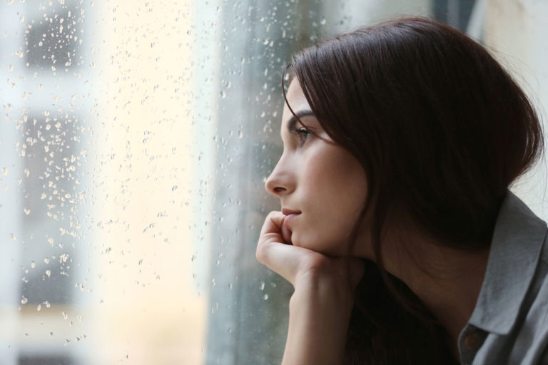 woman looking out of the window on a rainy day