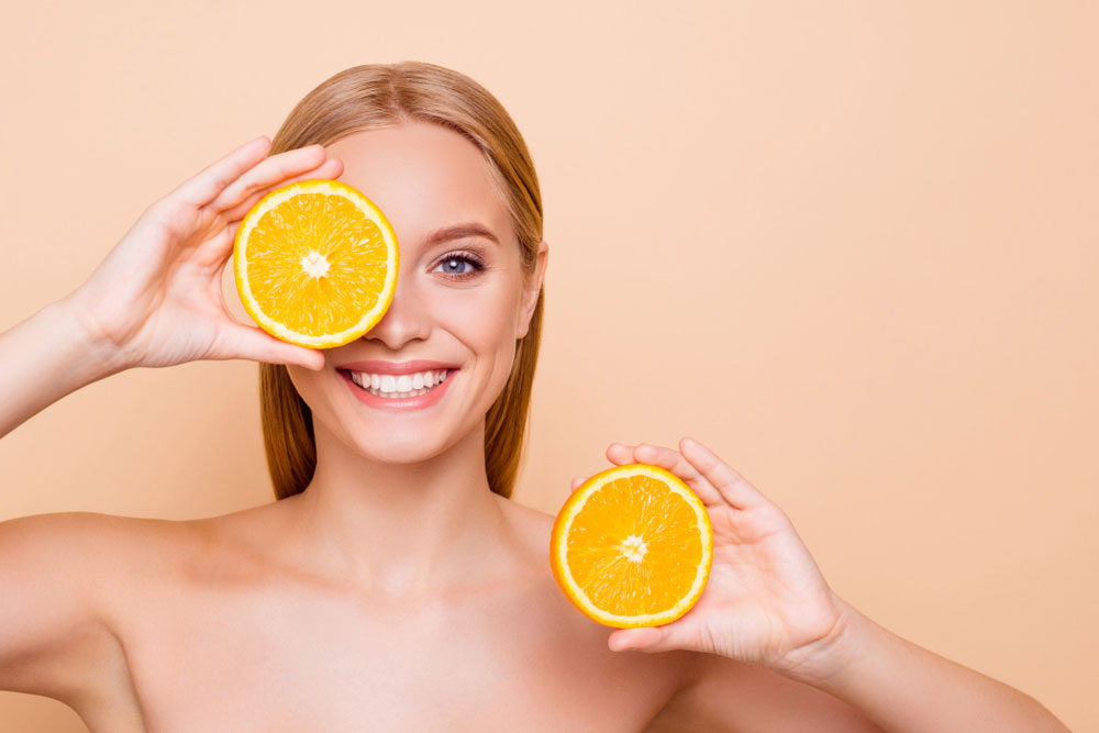 woman holding two oranges up to her head