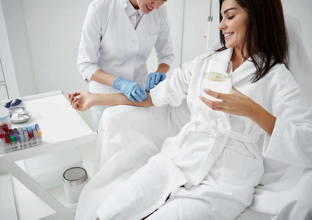 woman receiving iv hydration therapy while drinking lemon water