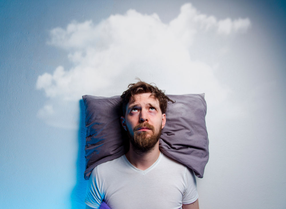 man with a pillow and clouds in the background