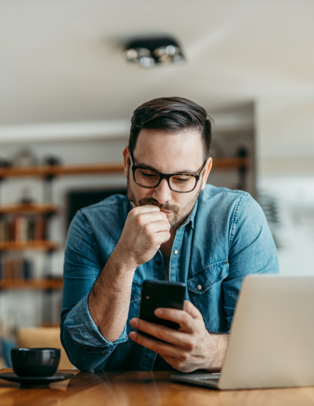 man on his phone at home with coffee and computer