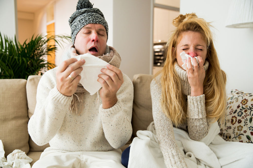 man and woman sitting on the couch with a cold