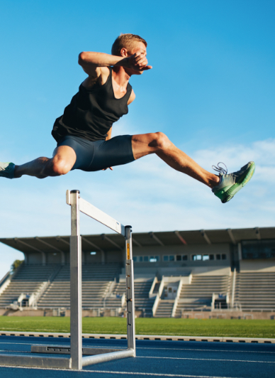 man jumping over a hurdle on a track