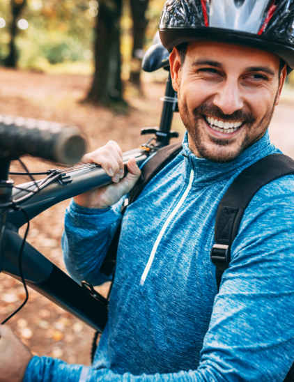 man holding a bike in the woods
